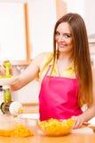 Woman making orange juice in juicer machine Royalty Free Stock Images