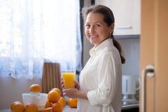 Woman making orange juice. Smiling middle-aged woman preparing orange juice in   kitchen royalty free stock images