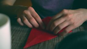 Woman making origami paper crane. From red napkin. Place mat on table in cafe stock video footage