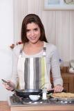 Woman making pancakes. A young woman making pancakes Stock Image