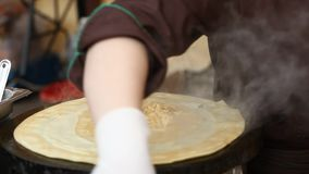 A woman making a pancakes at street market stock video footage