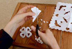Woman making paper snowflakes at a wooden craft table Royalty Free Stock Image