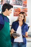 Woman Making Payment Through Mobilephone In. Happy women making payment through mobilephone while salesman holding electronic reader in hardware store Royalty Free Stock Photography