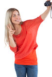 Woman making peace sign while taking a picture of herself Stock Photos