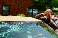 Woman making a phone call next to damaged car after a car accident. Woman making a phone call next to broken windshield after a car accident person crash royalty free stock images