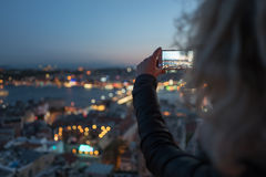 Woman is making photo on her phone of Istanbul from Galata Tower viewing platform Stock Photo