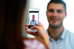 Woman making photo of a man on smartphone Royalty Free Stock Photography