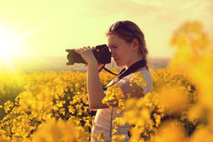 Woman making photos of rapeseed field with digital camera. Royalty Free Stock Images