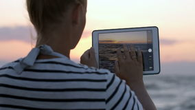 Woman making photos of sea waves with pad. Back view of a woman taking pictures of rough sea waves during sunset using tablet computer stock footage