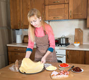 Woman making pizza at home kitchen. stock photo