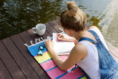 Woman making plans, taking notes in calendar or writing in her diary lying on the pier and drinking hot coffee. Daydreaming, plann Stock Photo