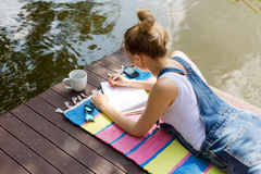 Woman making plans, taking notes in calendar or writing in her diary lying on the pier and drinking hot coffee. Daydreaming, plann Stock Image
