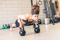 Woman making push ups on the kettle bells. In a gym. concept about fitness, sport and people Royalty Free Stock Image
