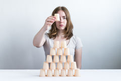 Woman making a pyramid from little plastic glasses Stock Photography