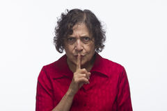Woman making a quiet gesture, horizontal. Older woman making a quiet gesture, horizontal Royalty Free Stock Images