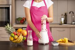 Woman making raspberry smoothie in a blender royalty free stock image
