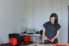 Woman making red leather wallet at atelier. Craftswoman making red leather wallet at atelier. Concept of creative handmade goods and home business Royalty Free Stock Photography