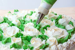 Woman is making rose from cream. Making rose and leaves from cream for cake decoration stock images