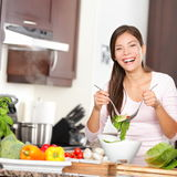 Woman making salad in kitchen. Smiling and laughing happy and cheerful. Beautiful young multiracial Caucasian / Chinese Asian young woman at home Royalty Free Stock Photography