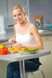 Woman making salad at kitchen royalty free stock image