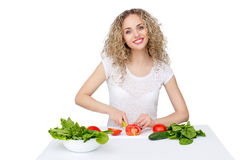 Woman making salad in kitchen. Healthy eating lifestyle concept with beautiful young woman cooking in her kitchen Royalty Free Stock Photo