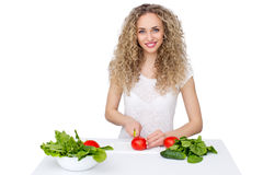 Woman making salad in kitchen. Healthy eating lifestyle concept with beautiful young woman cooking in her kitchen Stock Photography