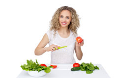 Woman making salad in kitchen. Healthy eating lifestyle concept with beautiful young woman cooking in her kitchen Royalty Free Stock Images
