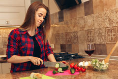 Woman making salad in kitchen. Healthy eating lifestyle concept with beautiful young woman cooking in her kitchen Stock Images