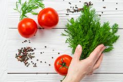 Woman making salad. Making salad closeup. Woman takes fresh dill from wooden table above view Stock Photo