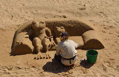 :Woman making sand sculpture of Frog sitting on sofa on Cascais beach. Stock Photo