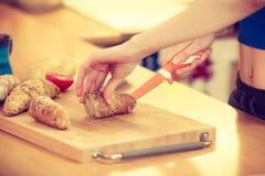 Woman making sandwich cutting bread Royalty Free Stock Photo