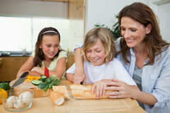 Woman making sandwiches with her children Stock Images