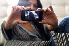 Woman making self photo with her smartphone. Focus on phone. Royalty Free Stock Image