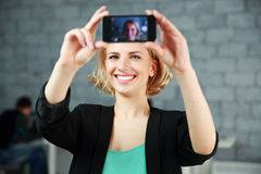 Woman making a self photo by her smartphone Royalty Free Stock Photography