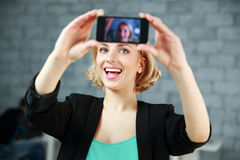 Woman making a self photo by her smartphone Royalty Free Stock Images