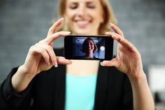 Woman making a self photo by her smartphone Stock Images