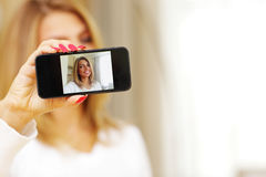 Woman making self-photo on smartphone Royalty Free Stock Photo