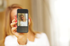Woman making self-photo on smartphone Stock Photography