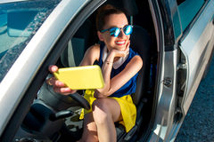 Woman making self portrait in the car. Young smiling woman in colorful clothes and sunglasses making self portrait sitting in the car Stock Photography