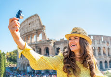 Woman making selfie in front of colosseum in rome Royalty Free Stock Photography