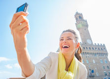 Woman making selfie in front of palazzo vecchio Stock Images