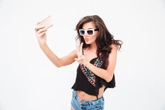 Woman making selfie photo and showing peace sign Stock Images