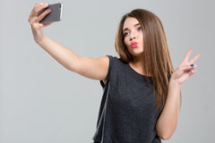 Woman making selfie photo on smartphone and showing peace sign Stock Photos