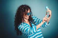 Woman making selfie with smartphone isloated on blue background stock image