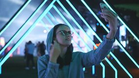 Woman on a neon party in the open air leads storis on smartphone. Woman making selfie on smartphone on neon party in the open air stock footage
