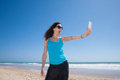 Woman making selfie teasing at beach. Portrait of brunette woman with black sunglasses and blue cyan shirt teasing sticking out tongue making selfie with mobile stock photo
