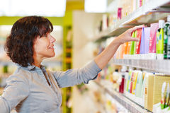 Woman making shopping decision in drugstore stock photos
