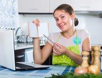 Woman making shopping list at kitchen Stock Photos