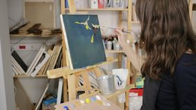 Woman is making a sketch of image by brush and paints on black canvas. Young female artist is depicting abstraction composition on canvas in workshop. She is stock video