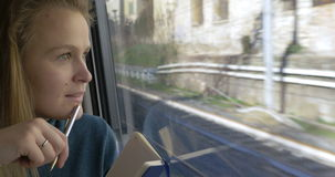Woman making sketches during train ride stock footage